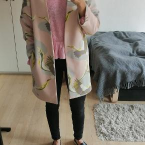 Kimono jakke med traner. Den har lommer i siderne og holdes åben