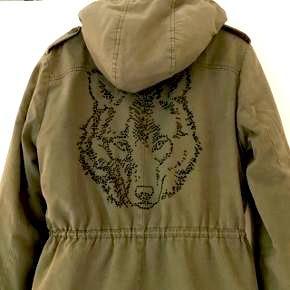 Armygrøn Sofie Schnoor trekvart lang frakke med teddybear for, samt termofor i ærmerne og smukt ulve motiv på ryggen. Der mangler en knap på det ene ærme og prisen er sat derefter.