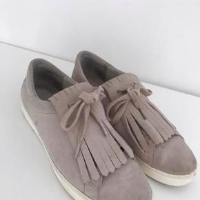 Sneakers fra Michael Kors. Velholdte, men brugte. Nypris var 1600 kr. Str 39. Frynserne på den forreste del af skoen kan tages af og på. Dette kan ses på billederne.