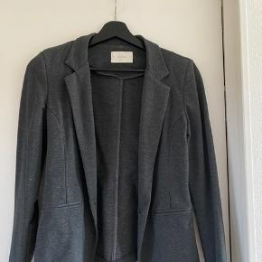 Smuk og elegant blazer fra Neo noir i mørk grå. Den kan bruges både til hverdag og fest