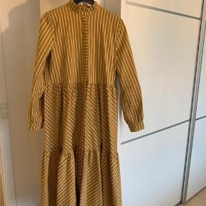 Flot, lang gestuz kjole i karrygul med hvide striber og guldsyning i striberne. I rigtig fin stand fra et ikke ryger hjem. Prisen er fast.