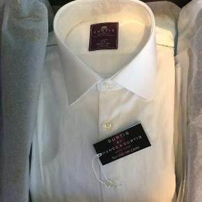 Klassisk flot hvid herre skjorte med cut away krave og ærmer til manchetknapper. Skjorten er fra London og købt hos Hawes & Curtis. Slim fit. Str. X-large. Str. 46-48. Aldrig brugt. Købt for stor. Kommer i original kasse.