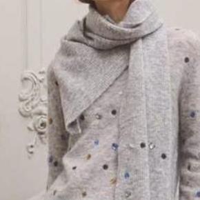 """Ualmindelig smuk lys gråmeleret Gustav sweater, overstrøet med små broderier og """"diamanter"""" i blå og gyldne nuancer. Sweateren er strikket i en blød og lun uld/mohairkvalitet, der er let og behagelig at have på. Perfekt som den er - og super over skjorter og kjoler.  Materiale: 42% uld, 28% mohair, 28% nylon og 2% elastan.  Helt ny og med mærke på endnu Str. 34 men 36 og lille 38 vil jeg sige evt også kan passe den 💕🌸"""