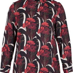 Brand: Zizi Varetype: Skjorte Farve: sort Oprindelig købspris: 349 kr.  Skjorten har lange ærmer med knaplukning. Skjorte blusen har et regular fit. Halsen er stolpelukning med knapper.