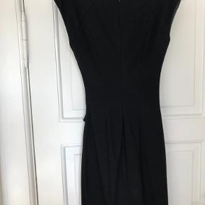 Lækker sort tætsiddende kjole fra Tiger of Sweden med rynkeeffekt ved maven. Sidder helt tæt til kroppen, lidt elastik effekt i stoffet.