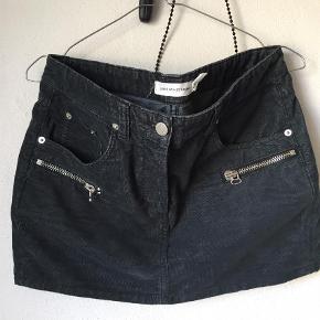 Varetype: Lækker kort nederdel med zip detaljer Størrelse: 38 (34+36) Farve: Dark grey Prisen angivet er inklusiv forsendelse.  Kort nederdel i let fløjs med fede lynlås detaljer.  Fed med strik og strømpebukser om vinteren, støvler eller sneakers.    Bytter ikke Sælges inkl. forsendelse.