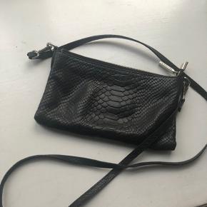 Sælger denne fine hverdagstaske fra Decadent. Tasken kan bruges som crossbody, men har aftagelig rem, så den også kan bruges som en clutch.  Tasken er brugt i en kort periode, men er i fin stand.