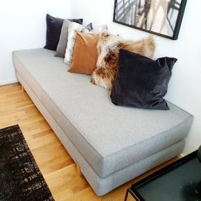 """Velholdt og praktisk sovesofa i grå-meleret uldfilt og med egetræsben fra ILVA. Tilsvarende model hedder """"MYK"""" og koster 6299,- dette er dog den gamle model uden tilhørende ryghynder. Måler 200 lang x 80 bred x 42 høj (udslået mål 200 x 160 x 21).   Afhentes ved Amager Strand"""