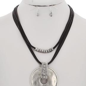 Mørkebrun dobbelt snøre halskæde med sølvperler og stort vedhæng i antik look.  Længde: 49 cm Matcende øreringe  PRISER ER INKL. LEVERING I DK