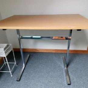 Lille køkkenbord med stålben der er afslag på kanten