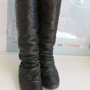 Lange støvler fra ShoeBiz i str. 37, men en stor str. 36 (som jeg selv er), kan også passe dem.  De er brugt en enkelt vinter, men de er meget velholdte, og læderet er blevet plejet løbende. Der er isat svangstøtte fra skomageren, men disse kan nemt afmonteres, hvis det ønskes.  Sålen er lavet af rågummi og er ikke specielt slidt, men der er kommet lidt knubs på læderet nede ved hælen (se sidste billede), dog ikke noget der har gjort dem utæt ifølge min erfaring med støvlerne.  Nypris var 1300, de sælges for 375 kr. plus fragt