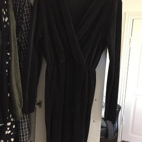 Sort, wrap-look kjole fra Club L. Brugt en enkelt gang og fra ikke-ryger hjem :-) Kjolen er med elastik i taljen, og ser derfor meget lille ud på billedet, men passer en str. 46 perfekt :-)
