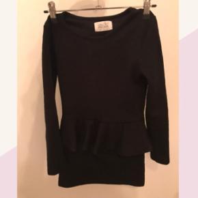Dette er en rigtig flot sort kjole med et lille slags skørt. Bare byd :)