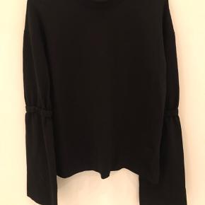 Enkel sort bluse med store ærmer.