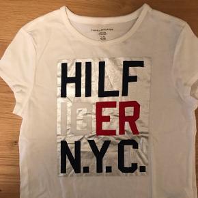 Hvid Tommy Hilfiger t-shirt, med sølv print. Aldrig brugt. Str 12-14 år Kan sendes hvis køber betaler fragten.