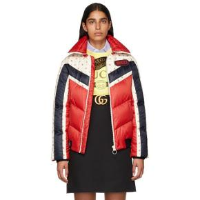 Varetype: 100% AUTHFloral Stripe Puffer Jacket in Red Retro 80s Inspired €2799Størrelse: 38 / 40 / 42 Farve: Rød Oprindelig købspris: 21000 kr. Prisen angivet er inklusiv forsendelse.  Gucci combines heritage classicism with modern elements as seen in the Floral Stripe Puffer Jacket, crafted from nylon with goose down padding, featuring striped retro inspired panel construction with floral print, bold rubber logo patch and funnel collar.  The outer layer is brought out as a fundamental silhouette for Pre-Fall 2018, and is being adapted as a leading piece of the final look.  This down jacket has design elements that speak to the styles popular in the 80s.  The Gucci logo is displayed in a graphic font that draws inspiration from the SEGA logo.   The Gucci stamp print lining.   Hibiscus red chevron quilted nylon with rosebud print detail.  Blue chevron tape detail.  Down feather goose padding.  Gucci in SEGA font, used with permission of Sega Holdings Co. Ltd.   Knit rib waistband and cuffs. Front pockets. Zip closure.  100% polyamide.  Material: Polyamide.  Color: red  Nylon fabrication Goose down padding Retro inspired panel construction with floral print Bold rubber logo patch Exposed central zip fastening Funnel collar A symmetrical slip pockets Ribbed hem Made in Italy Relaxed fit Model is 5ft 9.5 in / 1.76m and wears size 38