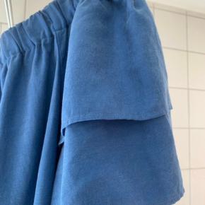 Smuk off shoulder top med de fineste ærmer og i en skøn lys petrolium / blå. Elastik kant øverst, så den er behagelig at have på.