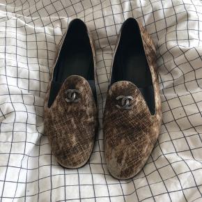 Fantastiske Chanel sko i ruskind sælges - så behagelige at have på. De er blevet brugt flittigt, hvilket afspejles ved standen; sålene kunne trænge til en udskiftning og noget af ruskindet er falmet flere steder på skoene og gået en anelse af bagpå højre sko. Nypris er 5600kr, og de sælges på baggrund af standen til 600kr. Størrelse 38, og tilsvarede sin størrelse. Chanel dustbag og authenticity card fra Vestiarie Collective medfølger.