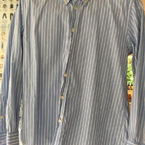 Varetype: Skjorte Størrelse: 12år Farve: Blå og hvid Prisen angivet er inklusiv forsendelse.  Bredde: 48 cm.    Længde:58 cm.
