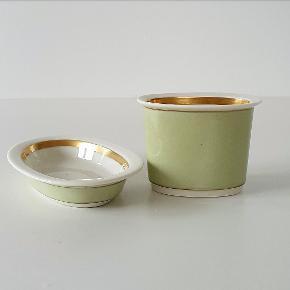 Bæger med underskål fra Royal Copenhagen i smuk farve og med fin intakt guldkant - til smykkerne på natbordet eller vatpindene på badeværelset. Bæger måler 7x7,5x5 cm. Underskål måler 11x7,5x2 cm. Sættet er fra 1946 og er i perfekt stand.