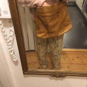 Vintage skuldertaske i cognac farvet læder. Har en lynlås lomme bagpå, lomme foran, 1 lynlås lomme indvendigt+ 2 små åbne lommer. Måler ca 33 x 44 cm