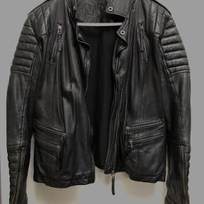 Få et rå og feminint look med den seje biker læderjakke i høj kvalitet, blødt sort læder. Jakken har quiltede detaljer på skuldrene ærmer smat lynlås ærmerne. 100% fåreskind   Jakker er brugt/patineret  Pris er sat efter stand