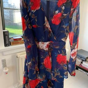 Flot blomstret kjole, brugt én gang sidste jul.  Jeg sælger den da jeg desværre ikke kan passe den længere. Kjolen er smal omkring brystet og har en flot v udskæring  Brystmål: 35cm Længde: 80cm Størelse: S, UK 8, US, 4, EU 36. Efter min mening er den en lille S eller stor XS