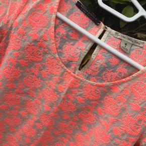 Skøn bluse med pink broderi. Lille knap i nakken. Brugt 1-2 gange.  Maison Scotch