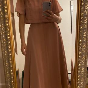 Festkjole med åben ryg i den flotteste rosa farve.  Kjolen er i en model til høje piger, er selv 177 cm. Høj.  Kraven er fyldt med palietter.   Den er aldrig brugt, da det er et fejlkøb.    - Forhandler kun med MobilPay.  - Køberen betaler for porto - 39 kr.
