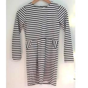 En sort og hvid stribet kjole med lommer i og lynlås bag på ryggen. Den er blød. Brugt 3 gange.