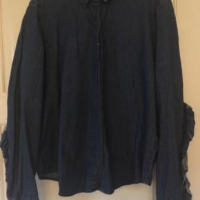 Skøn denim skjorte med flossede flæser på ryg og ærmer. Længde 63 cm.