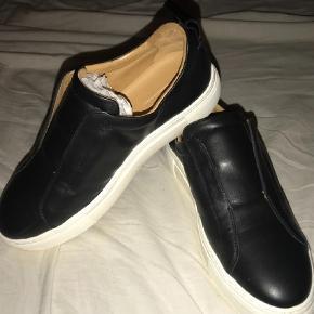 Varetype: Sneakers Farve: Sort Oprindelig købspris: 1795 kr.  Hej   Jeg sælger mine helt nye By Malene Birger Snekers  Som set på billede er de aldrig brugt ( der er ikke fodaftryk i skoen)  Og sko bunden er Helt ren og hvid   Der medfølger en dustbag ( se billede )   De fitter en str. 39   Mega fede snekers  Det er modellen med elastik  Skoene er læder sko  Kvittering haves ikke   Byd endelig er åben for alle bud!