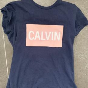 Mørkeblå Calvin Klein t-shirt med tryk i lyserød. Som man også kan se på billedet er  den lidt slidt ved bogstaverne. Skriv pb for flere billeder eller mere info!🤩 Byd gerne!:)