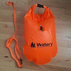 Watery havtaske til åbent vand. Lavet i slidstærkt PVC materiale. Udvendig mål: 64x30 cm  Tasken er inddelt i to rum: Et vandtæt rum til opbevaring samt et rumt der pustes op, så tasken flyder på vandet. Derudover sele til at spænde rundt om maven så der kan svømmes uforstyrret af tasken.  Tasken har været pustet op, men aldrig brugt. Købt på watery.dk
