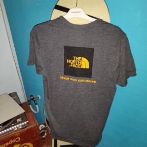 The North Face t-shirt. Den er blevet vasket en del, hvilket den er blevet lidt faded af. Bemærk også lille hul i ærmet
