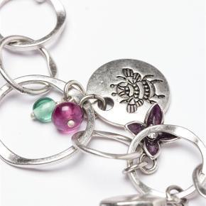 Varetype: -=NY=- GARDEN HALSKÆDE Størrelse: 42-51cm (Justerbar) Farve: Sølv Oprindelig købspris: 600 kr.  A&C JEWELLERY GARDEN HALSKÆDE  Skøn halskæde sammensat af sølvfarvet ringe med mange flotte vedhæng i grøn og lilla. Halskæden er fra Garden kollektionen, hvilket tydeligt kan ses på de søde vedhæng. Der er bl.a. et lille pindsvin, en snegl, flere små blomster, et blad, en lille hat, en vandkande og en planteskovl.    Længde: ca. 42-51cm (Justerbar)  Model: Garden Style: 2032-1405   Varens stand: aldrig brugt