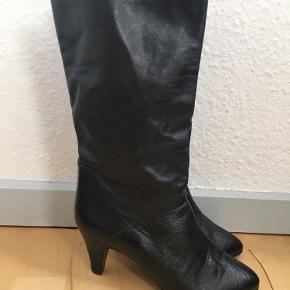Super fine lange sorte vintagestøvler med fine afrundede snuder og lille hæl i blødt læder fra Gabor. Formentlig fra 1980'erne. Str. 37. 100% ægte læder. De ser ikke ud til at have været brugt. Kom med et bud.  Varen befinder sig i 9520 Skørping. Sender med DAO.  Se også min øvrige annoncer. Jeg sælger tøj, sko og accessories. Pt er min shop fuld af vintagekup, high street fund og mærkevarer i mange forskellige str. Kig forbi og spøg endelig!!