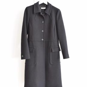 SMUKKESTE figursyede sorte Prada frakke i uld - ultimativ klassiker! Står stort set som ny og leveres selvfølgelig nyrenset. Brug den til de kølige sommeraftener, eller gem den til vinter - du vil ikke fortryde det!  Str IT44, men vurderer den til at passe en str S/M. Målene er som følger: Bryst 48 Talje 43 Hofte 53 Længe 106