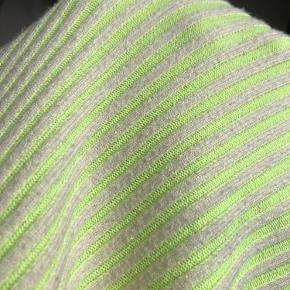 En enkelt sort plet. Kan nok fjernes med en god omgang pletfjerning, hvis man passer på selve farven på trøjen imens