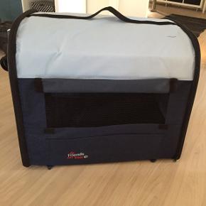 Lækker stof transportkasse til hund. Str 60x50x50 🐶 bund der kan vaskes.ALDRIG brugt da den er købt for stor. Kan klappes helt sammen og være i taske der medfølger. Prøver at sælge her da det for dyrt at returnere til firma. Har kvittering.