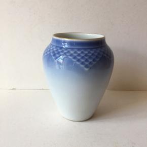 Enkel, smuk B & G vase af god kvalitet og meget anvendelig størrelse. Vasen, som er 1. sortering fra Bing & Grøndahl, er 12,5 cm høj og 10,5 cm i diameter. Vasen er i perfekt stand med intakt guldkant, den fremstår som ny.  Sendes gerne med GLS.