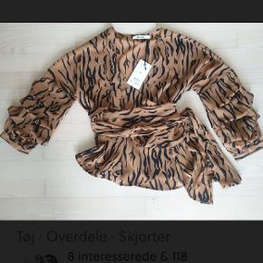 Ny bluse, str 38 med lange stropper til at slåom taljen. Selve blusen er lukket og kan strammes ind rundt og taljen.