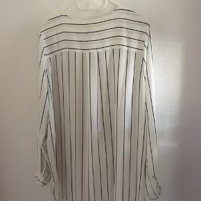 Stribet skjorte i sort og hvid En størrelse 40, men passer nok mere en størrelse 42 Fejlkøb - kun prøvet på Byd gerne