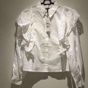 Britta shirt i hvid med smuk flæse kant med broderi anglaise. Ny stadig med tag