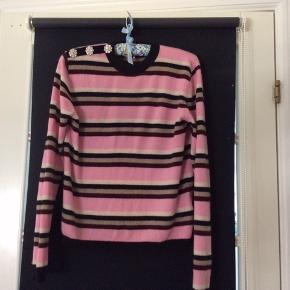Super flot Ganni Multicolor Pullover. Pink sweater i premium cashmere med flerfarvede striber. Trøjen har rund hals samt tre knapper med krystalpynt og GANNI logo på højre skulder. Let cropped model med almindelig pasform og blød, retstrikket kvalitet med ribstrikkede kanter. Materiale - 100% Cashmere  Helt ny- Aldrig brugt.   Købspris 2499 kr - Sælges for 550 kr inkl fragt på mobilepay. Sendes forsikret med GLS.  I er også velkommen til at byde😊