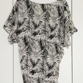 100 % NY: Skøn bluse i løs model med rynker under brystet. Rynkerne kan reguleres så blusen bliver mere/mindre bred.  Farve: Sort/hvid Materialet er polyester.  Brystvidde: 60 cm x 2 Længde: 75 cm  Ingen byt, og prisen er fast.