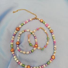 Smuk halskæde med ferskvands perler i alle regnbuens farver 160 kr pr stk Armbånd med guld perler 70 kr op til 18 cm Armbånd med ferskvands perler 75 kr op til 18 cm Nikkelfrit guldbelagt stål og messing, 18 karat guldbelagte perler, zirkonia, swarovskiog ferskvands perler  Prisen er fast  Produktions tid op til 7 dage