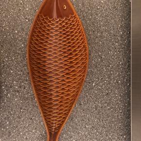 Fiskeformet fad i monokrom brunlig glasur.  Fadet er designet af svenskeren Stig Lindberg, og produceret i 1950'erne af Gustavsberg.  Fadet har et super fedt og antikt design, som passer perfekt ind i den retro og kreative indretning.   !Fadet er i ekstremt flot og intakt stand!  Mål: Længde: 31 cm, Bredde: 11 cm  Er åbent for bud og spørgsmål, så skriv endelig ved interesse.   Kan afhentes i Holstebro eller sendes på købers regning efter ønske.  Kan leveres i Holstebro/Herning omegn for lille merpris.