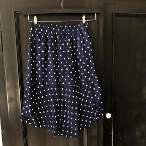 Mørkeblå nederdel med hvide prikker, elastik i taljen, str. S. Nederdelen er længere bagpå end foran