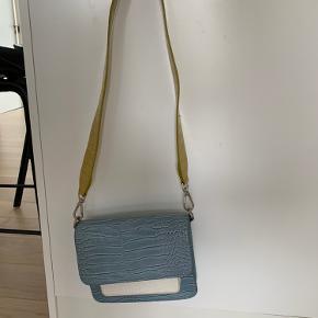 Hvisk Cayman Pocket Limited Edition Crossbody taske i blå, hvid og gul. Brugt med små slid - f.eks . ved lås, ellers flot stand.